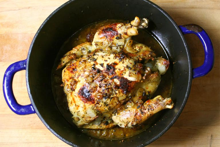 chicken being roasted in dutch pan